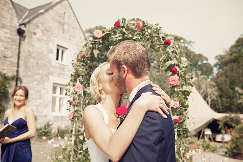 A Suzanne Neville Wedding Dress For a Teepee Humanist Wedding At Tros Yr Afon With A Red Rose Bouquet By Weddings Vintage.