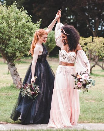 Autism marriage inclusive wedding inspiration with two brides in a black wedding dress and pink embroidered bridal separates