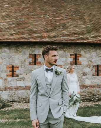 Portrait of the groom in a grey three-piece wedding suit with his bride in the background