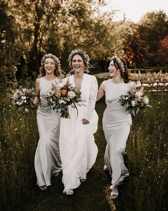 Bridesmaids in silver satin dresses and bride in a lace dress walking through the fields with a dried flower crown on their heads