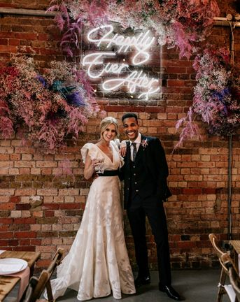 Prezola wedding couple standing in front of a neon happily ever after sign surround by pink gypsophila and wearing a ruffle sleeve wedding dress