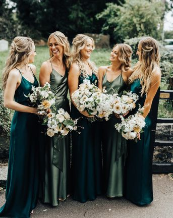 Bridal party in sumptuous satin bridesmaid dresses in different shades of green by Rewritten Bridesmaids.