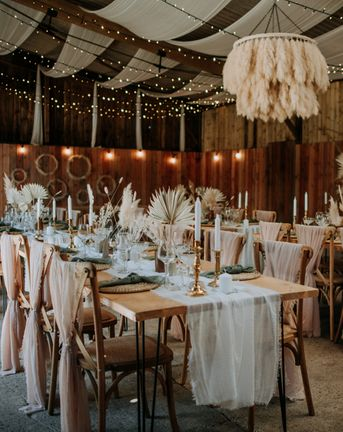 Romantic East Yorkshire Barns wedding reception with pink chiffon chair back decor, pampas grass chandelier, fairy light backdrop and dried palm leaf centrepieces