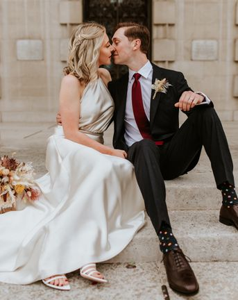 Bride in a champagne colour wedding dress kissing her groom on the steps at Leeds Civic Hall