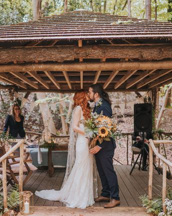 Outdoor forest wedding with sunflower wedding bouquet, embroidered veil and lace wedding dress.