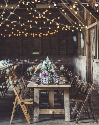 Rustic wedding ideas with fairy lights, trestle tables, tree slices, flowers in jars and wooden signs