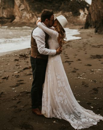 Seaside elopement with bride in a long sleeve lace wedding dress and fedora hat