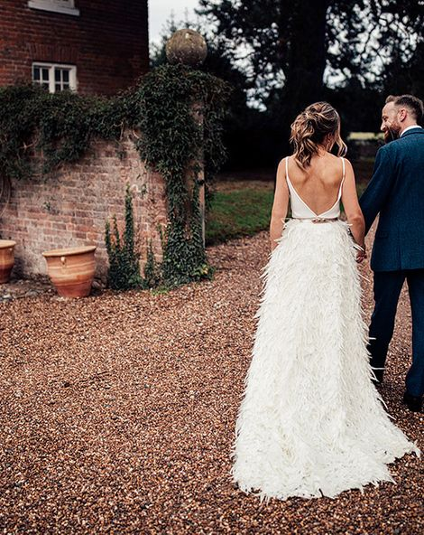 Charlie Brear Payton Bridal Gown & Piora Feather Skirt with Deep Red, Grasses & Pheasant Feather Floral Installation at Iscoyd Park, shot by Harry Michael
