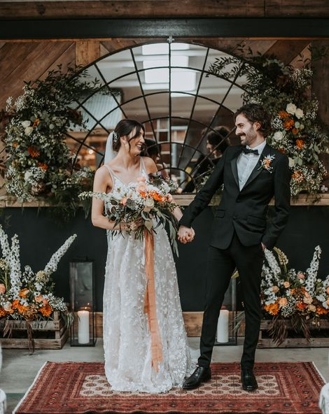 bride in a lace dress and groom in a black tuxedo at new Lake District wedding venue with oval micro back drop and colourful floral arrangements