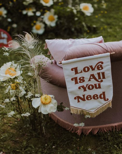 Love Is All You Need fabric banner resting on a velvet sofa surrounded by wildflowers for sixties wedding inspiration at a farm