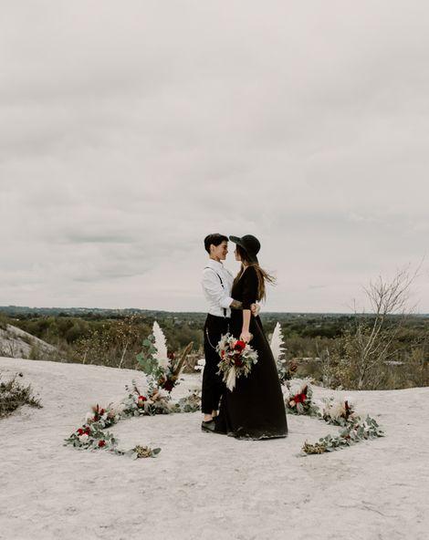 Black Wedding Dress for Wild Same-Sex Couple Wedding Inspiration | Pampas Grass, Eucalyptus & Red Rose Horseshoe Floral Design | Anne Letournel Photography