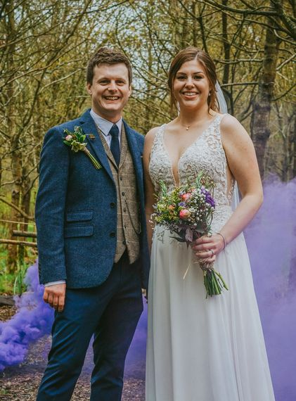 david lefebvre photography stunning dramatic smoke grenade image of bride and groom stood in purple smoke wearing navy blue tweed suit and decorative dress and fresh flowers at micro country wedding