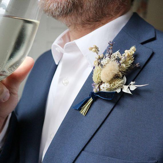 mary elizabeth flowers blue dried flower buttonhole on jacket