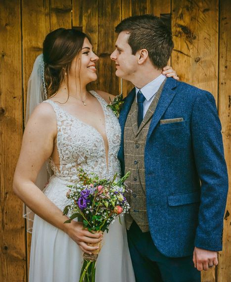 david lefebvre photography young married couple smiling at each other stood in front of wooden oak wall dressed in navy tweed suit and decorative classical low cut wedding dress