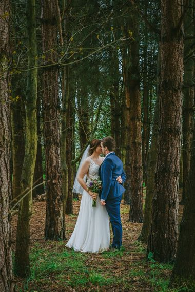 david lefebvre photography young married couple kissing in dramatic woodland setting wearing decorative white dress with fresh flowers and navy tweed suit at candid micro wedding with david lefebvre photography