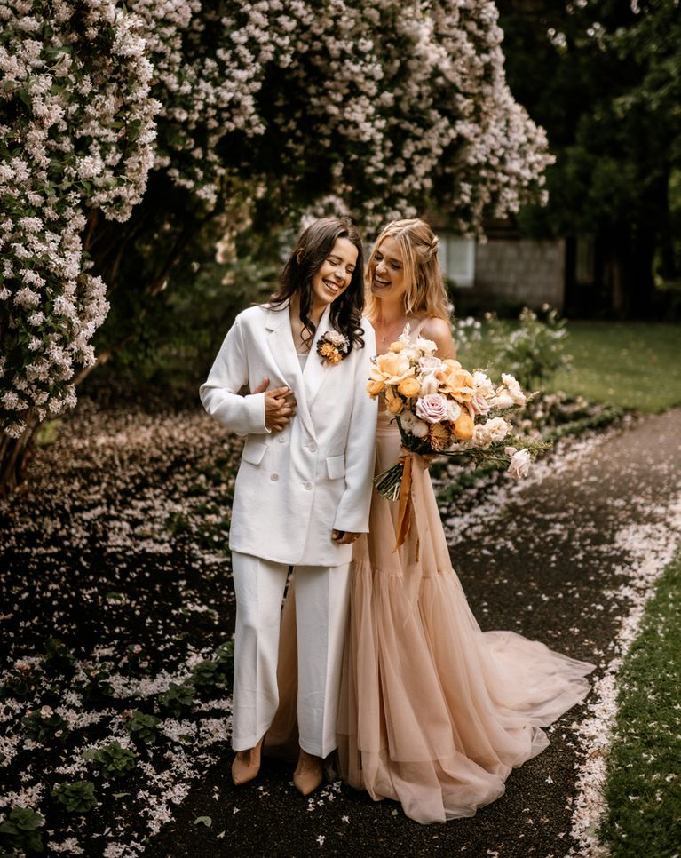 Honey yellow wedding inspiration with two brides in a peach wedding dress  and white bridal suit