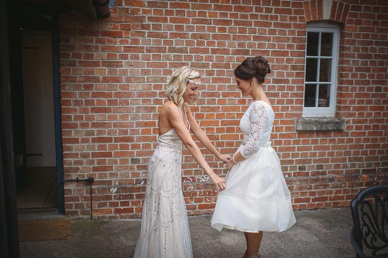 An English summer festival style wedding held in a Tipi Tent with a humanist ceremony with a bride in a Jenny Packham Luna dress and a bride in Miu Miu shoes and a Fur Coat No Knickers Bellini dress.