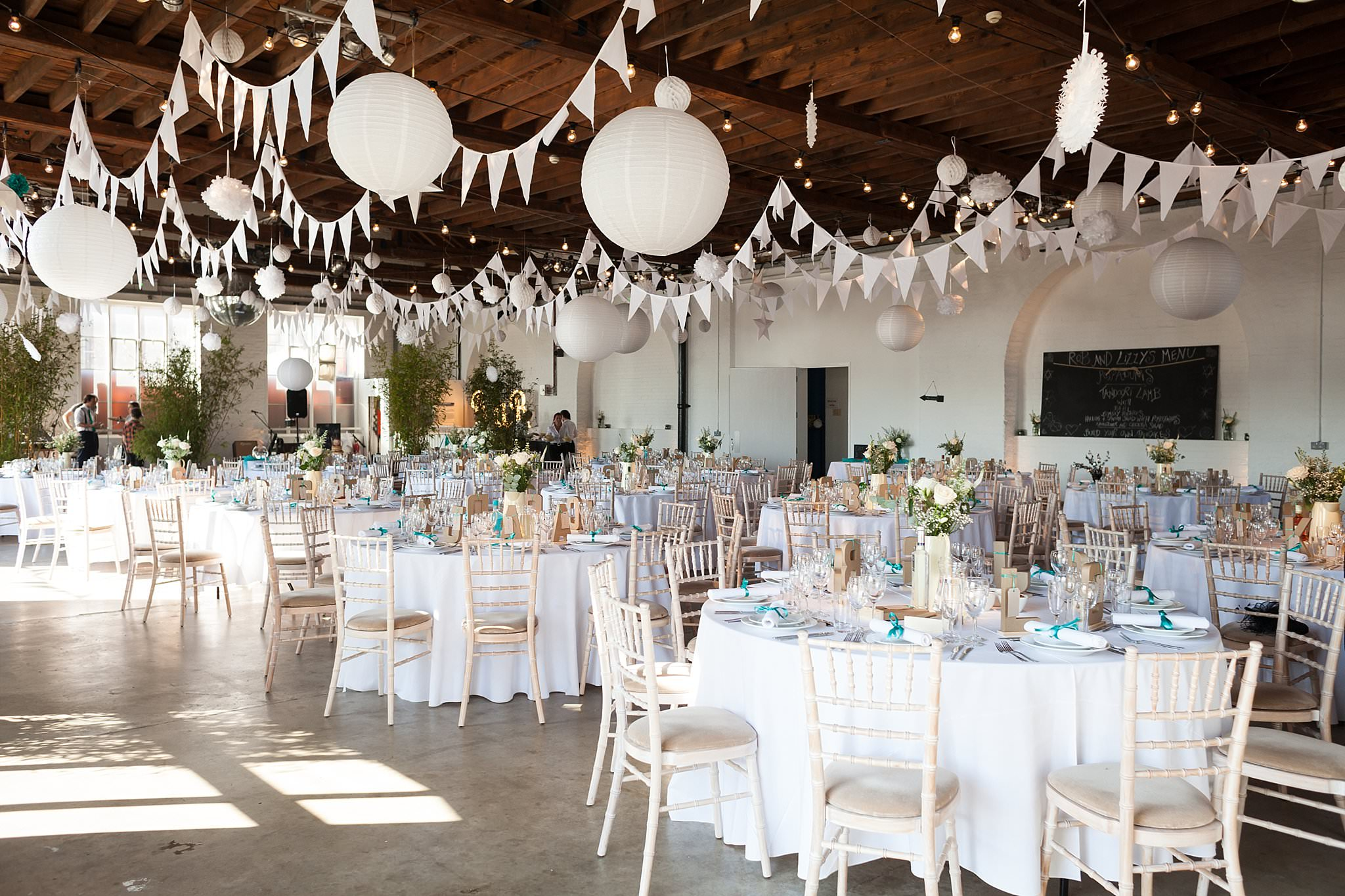 Trinity buoy wharf wedding with lace mon cheri bridal gown white bunting and hanging paper lanterns junglespirit Images