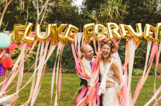 Pink and Peach Streamers, Gold Foil Balloons | Colourful Wedding Fiesta at Abbotsbury Wedding in Weymouth, Dorset | Decor from The Prop Factory | Bride in Made with Love | Photography by Paul Underhill.