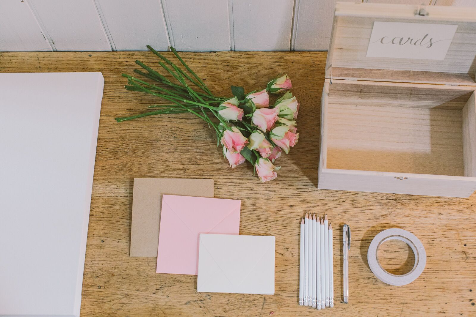 Wooden card box, white box canvas, colouful envelopes, pink roses and pencils, all resting upon a wooden table