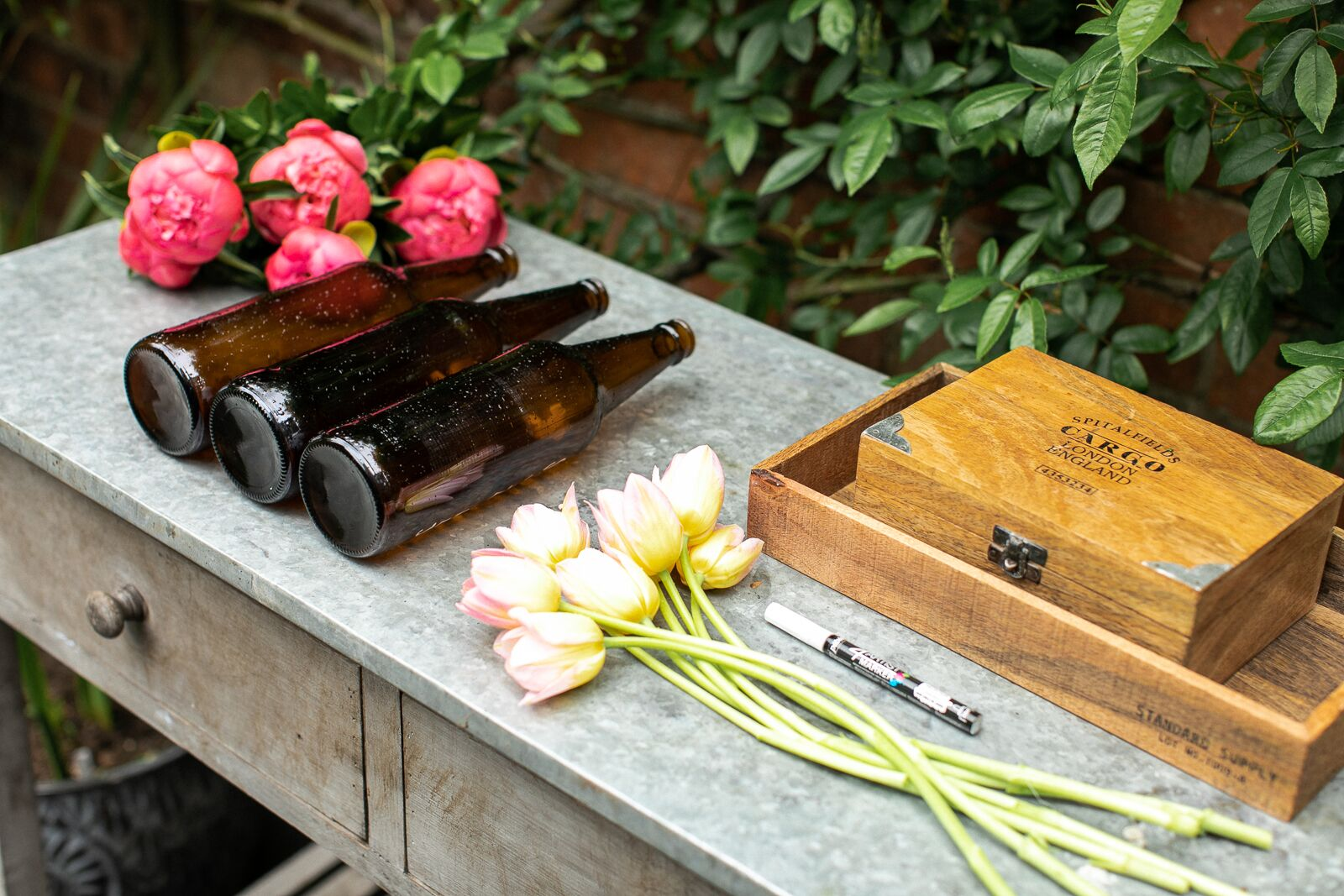 Items needed to create a bottle table plan for a wedding: brown glass beer bottles, flowers, a white pen and rustic boxes all resting on top of a limewashed console table
