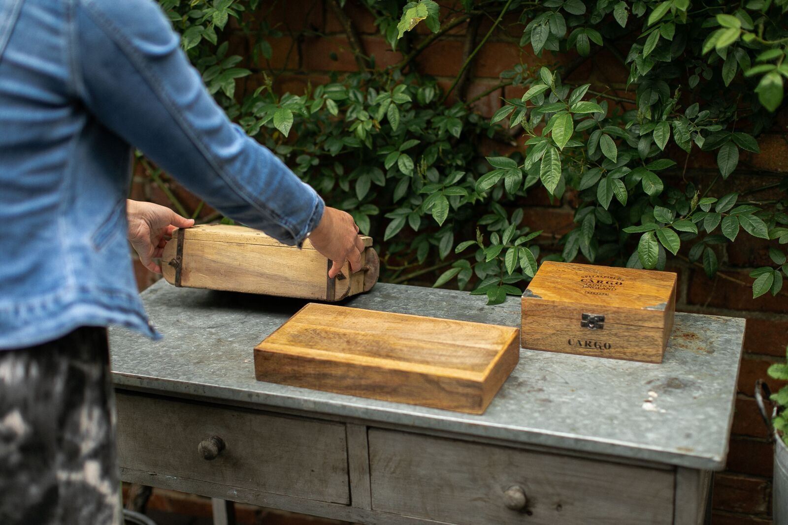 Person laying wooden boxes and crates upon a limewashed console table to make a base for a bottle table plan for a rustic wedding
