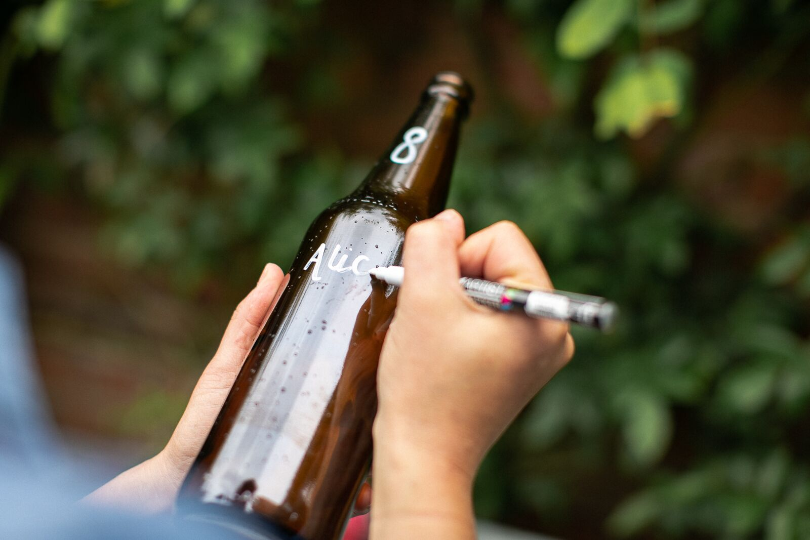 Person writing the name of a wedding guest onto a bottle using a Pebeo pen to create a DIY bottle table plan