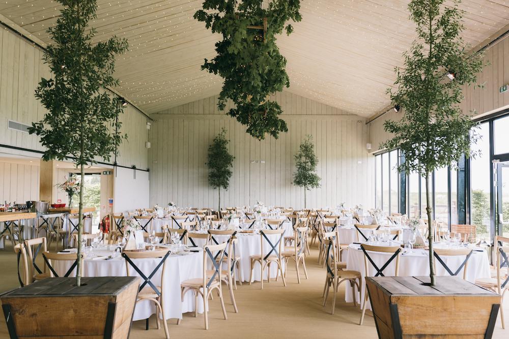 Bright Primrose Hill Farm barn wedding venue with indoor tree decor and round table reception