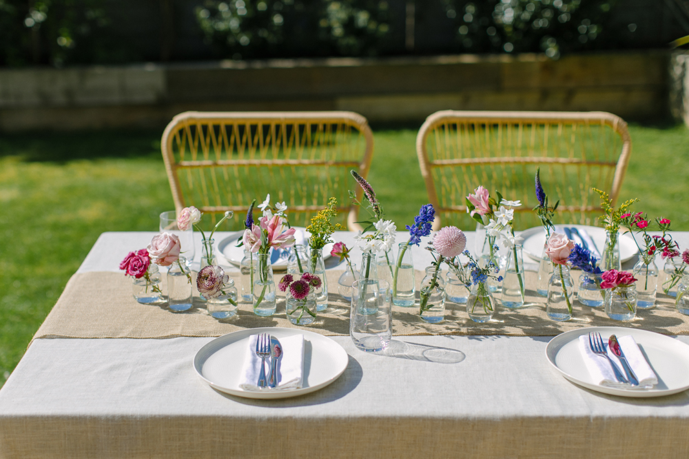 diy wedding centerpiece with mini glass vases and bottles and single stems of brightly coloured spring flowers on a linen tablecloth