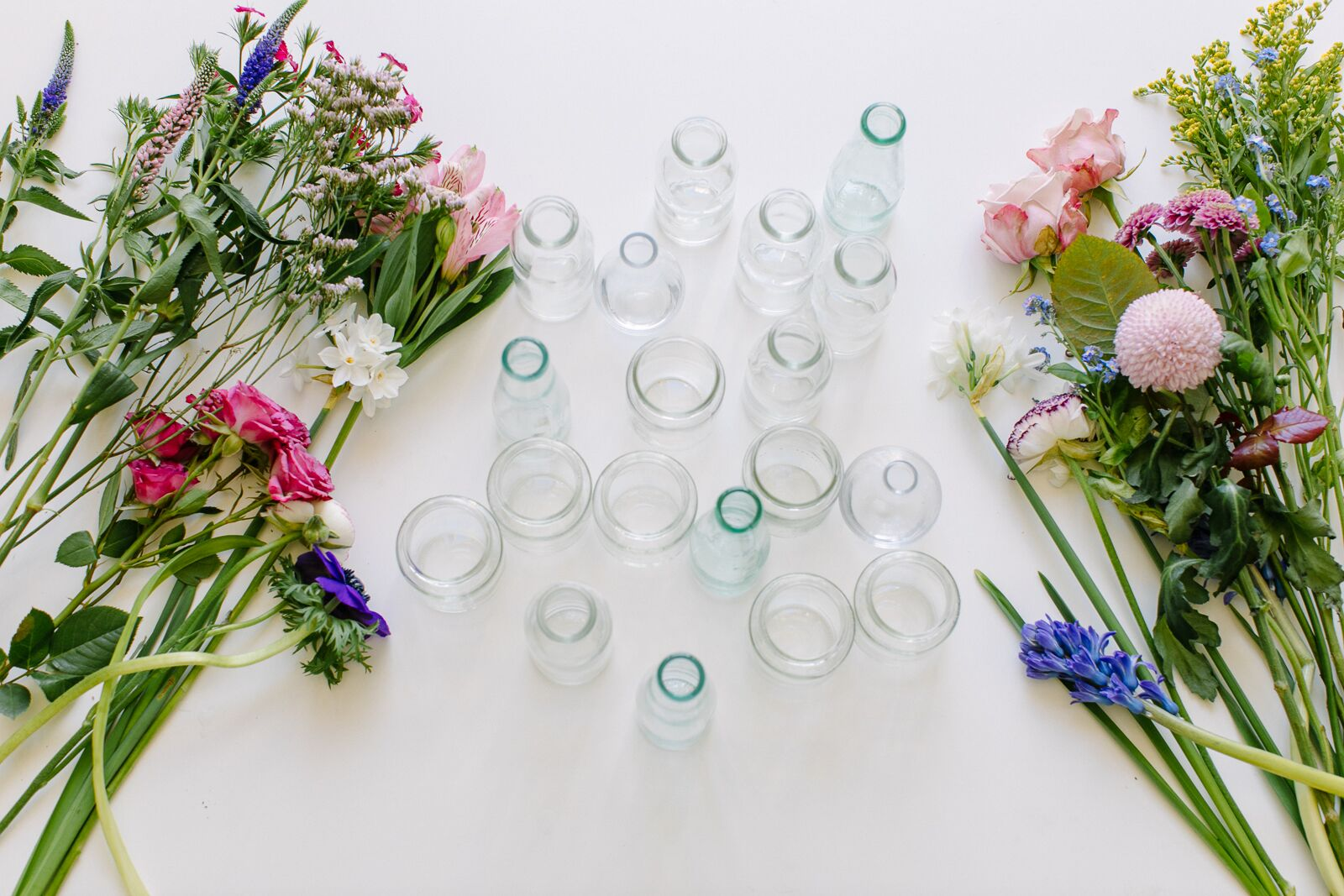 Spring flowers (narcissi, forget-me-nots, hyacinths, roses, ranunculus) laid out next to an assortment of clear glass bottles and vases of varying shapes and sizes