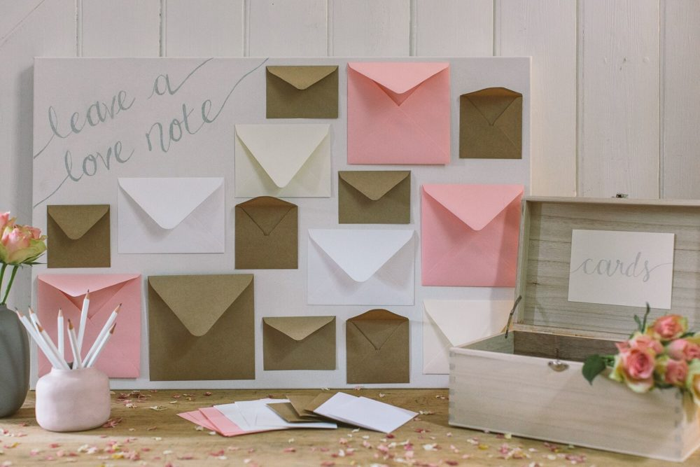 DIY wedding card table created using a box canvas, a card box, and envelopes for guests to leave a note to the bride and groom