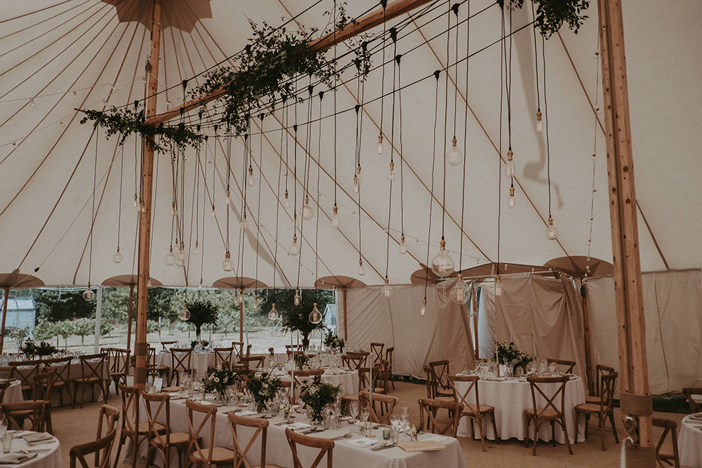 Marquee Wedding at Home on The Isle of Wight with Foliage and Edison Bulb Decor and Rime Arodaky Wedding Dress by Jason Mark Harris and Harris Films
