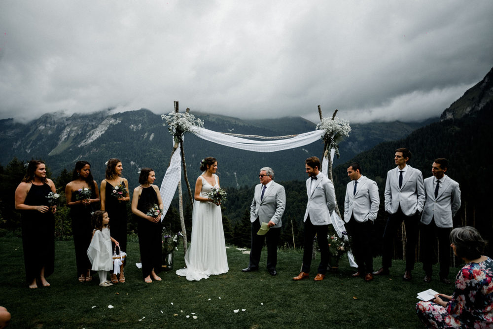 French Alps Wedding with Bride in Mariées Passion Wedding Dress, Bridesmaids in Navy Dresses and Groomsmen in Grey Jackets by Maël Lambla Photographer