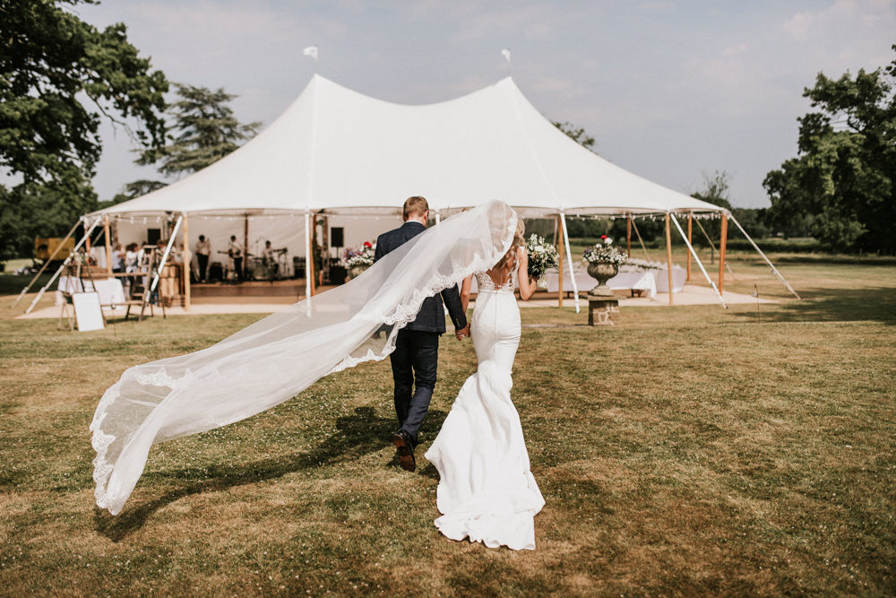 Vicenta Pronovias Wedding Dress for an Outdoor Tent Reception with BBQ Wedding Breakfast and Green and White Flowers by Holly Rose Photography
