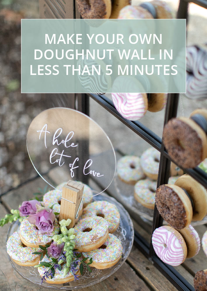 Doughnut wall for a wedding made out of a mirror and hooks, stood on a wooden table with a cake stand piled with doughnuts