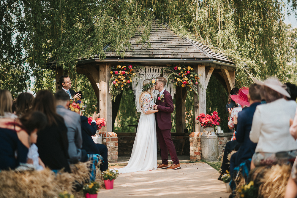 Outdoor Wedding Ceremony with Bride in Colourful Embroidered Luna Bride Wedding Dress and Groom in Burgundy Paul Smith Suit Standing in Front of Macrame and Flower Decorated Altar by Henry Lowther Photography