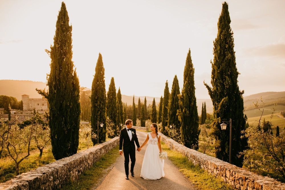 Italian Castle Wedding in Tuscany with Outdoor Wedding Ceremony and Reception Decorated with Floral Arch and Festoon Lights by Urška & Domen Photography