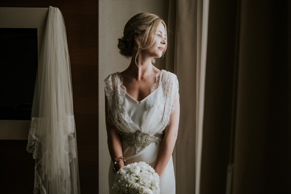 Bride in Halfpenny Wedding Dress with Embellished Belt for an Italian Destination Wedding with White Flower and Festoon Lights by Fotografica Mente