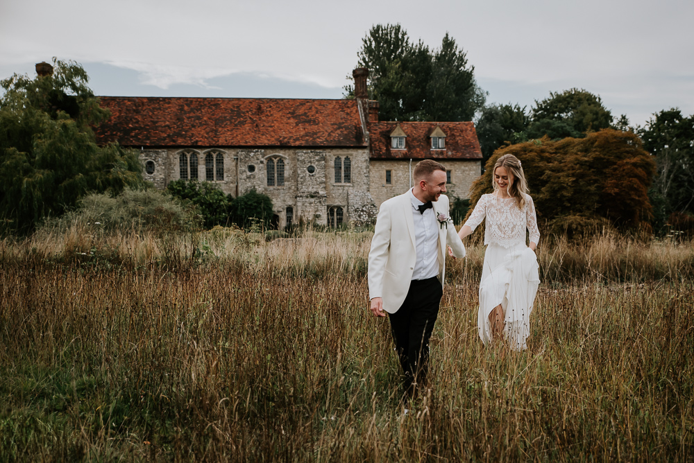 Groom in White Dinner Jacket and Bride in Separates for a Festival Wedding at Nettlestead Place in Kent by Michelle Cordner Photography