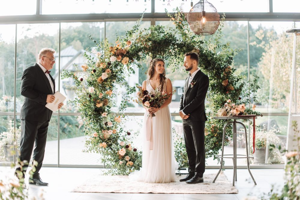 KATYA KATYA Wedding Dress & Knitted Coverup for a Latvia Wedding with Moon Gate Floral Arch and Aisle Wedding Flowers by Liene Peterson Photography