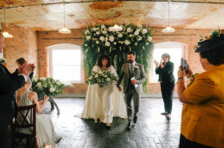 Bride and groom with floral backdrop - wedding checklist article